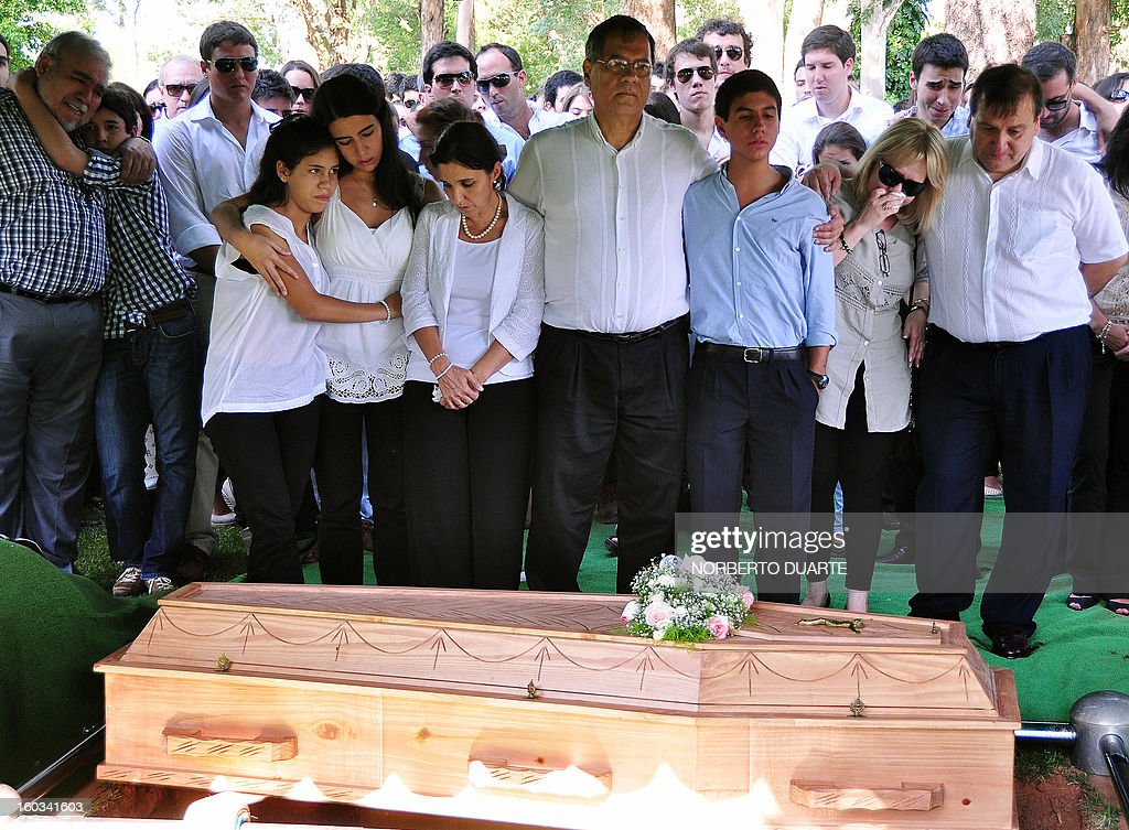 The parents (C) and siblings of Paraguayan student Guido Britez, 21, who died on a fire accident in a nightclub in Brazil, mourn next to his coffin during the funeral in Asuncion, on January 29, 2013. Britez died on January 27 during a blaze in a nightclub in Santa Maria, southern Brazil, which left 231 people dead and at least 100 others hospitalized, 80 of them in serious condition.