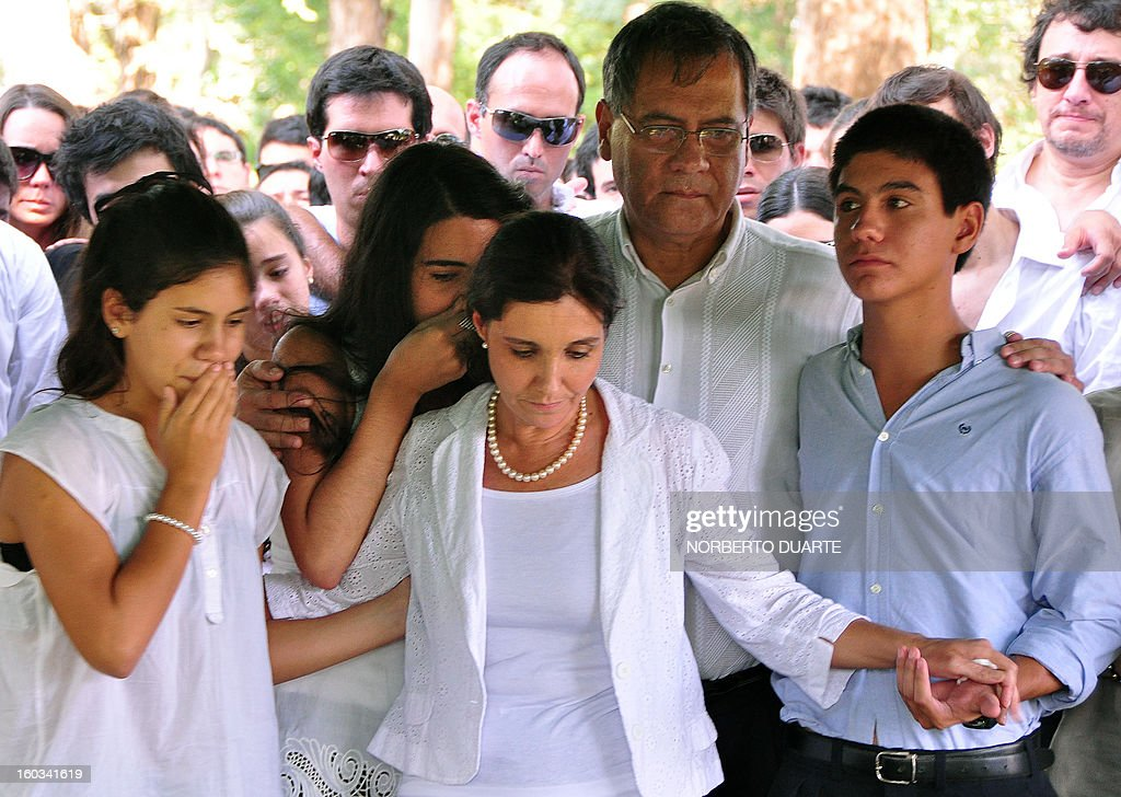 The parents (C) and siblings of Paraguayan student Guido Britez, 21, who died on a fire accident in a nightclub in Brazil, mourn next to his coffin during the funeral in Asuncion, on January 29, 2013. Britez died on January 27 during a blaze in a nightclub in Santa Maria, southern Brazil, which left 231 people dead and at least 100 others hospitalized, 80 of them in serious condition. AFP PHOTO/NORBERTO DUARTE