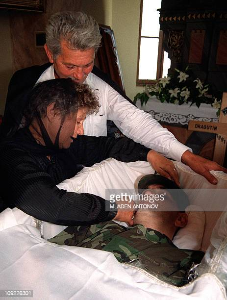 The parents of a dead Croatian soldier killed by Serbian nationalists two days before cry on his deathbed just before the funeral 06 July 1991 in...