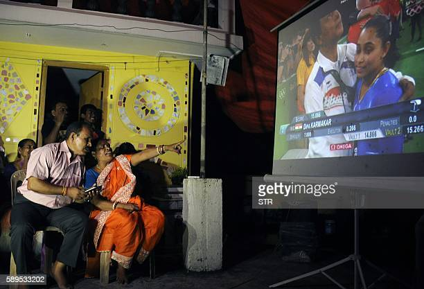 TOPSHOT The parents of Indian gymnast Dipa Karmakar Dulal Karmakar and Gouri Karmakar alongwith family members watch a projector screen in Agartala...