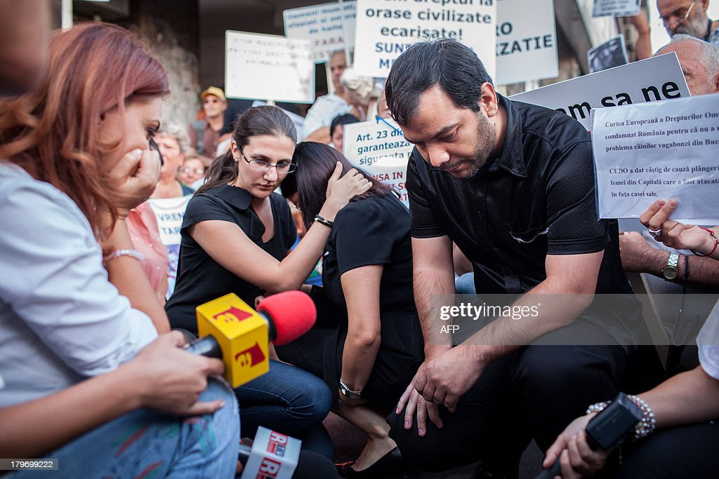 The parents of Ionut Anghel, a four year-old who was killed by five stray dogs earlier this week, join protesters in a moment of silence during a rally organized to demand that the authorities come up with a solution to the stray dog population in Bucharest on September 6, 2013.