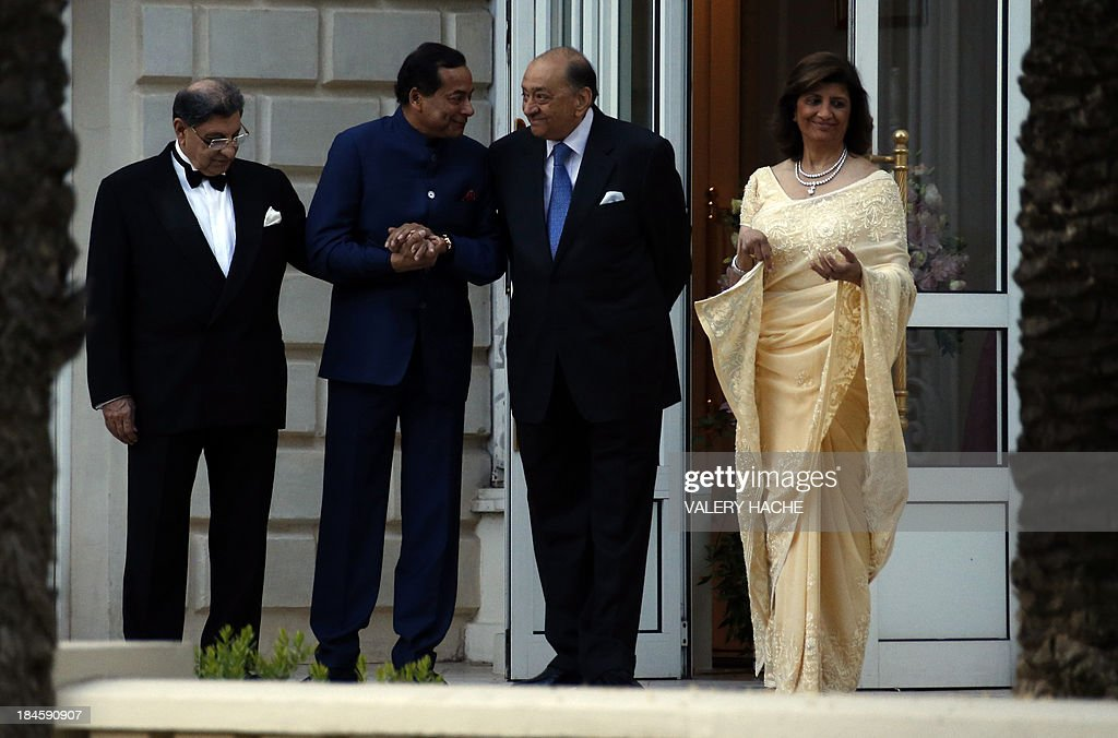 The parents of the groom Kunal Grover greet guests outside the Carlton Hotel in the southeastern French city of Cannes on October 14, 2013 during his wedding party. The Carlton palace was entirely booked for several nights to accomodate guests for the wedding of Grover and Ria Dubash.