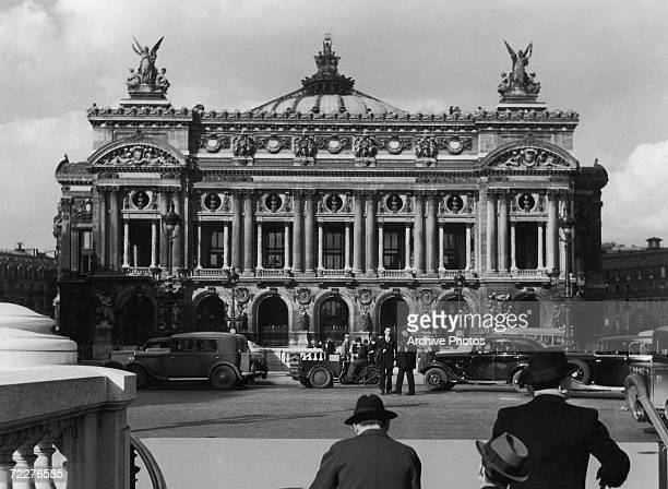 The Paris Opera House and traffic on the Place de l'Opera Paris circa 1935 Designed by architect Charles Garnier the opera house was completed in 1875