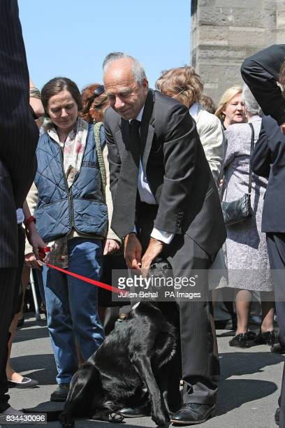 The partner of Nuala O'Faolain John LowBeer and dog Mabel at the funeral of Irish writer O'Faolain from the Church of Nativity in Dublin