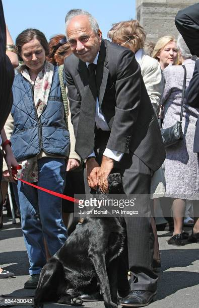 The partner of Nuala O'Faolain John LowBeer and dog Mabel attend the funeral of Irish writer O'Faolain from the Church of Nativity in Dublin
