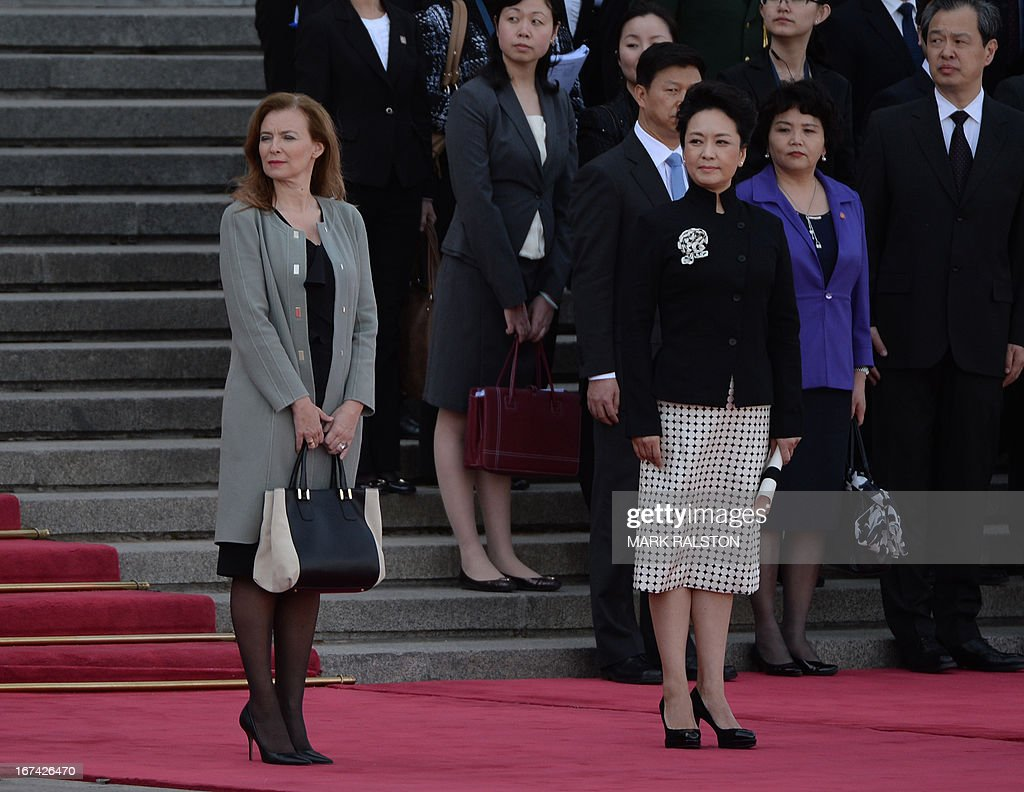 The partner of the French president, Valerie Trierweiler (L), and the wife of the Chinese president Peng Liyuan (front, C) watch as the leaders review an honor guard outside the Great Hall of the People in Beijing on April 25, 2013. French President Francois Hollande, accompanied by a high-powered business delegation, started a two-day visit to China, with trade rather than geopolitics at the top of the agenda. AFP PHOTO/POOL/Mark RALSTON