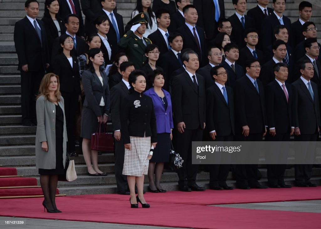 The partner of the French president, Valerie Trierweiler (L), and the wife of the Chinese president Peng Liyuan (front, C) watch as the leaders review an honor guard during a welcoming ceremony outside the Great Hall of the Peopleon April 25, 2013 in Beijing, China. Hollande has begun a two-day trade visit to China, bringing with him a large French trade delegation.