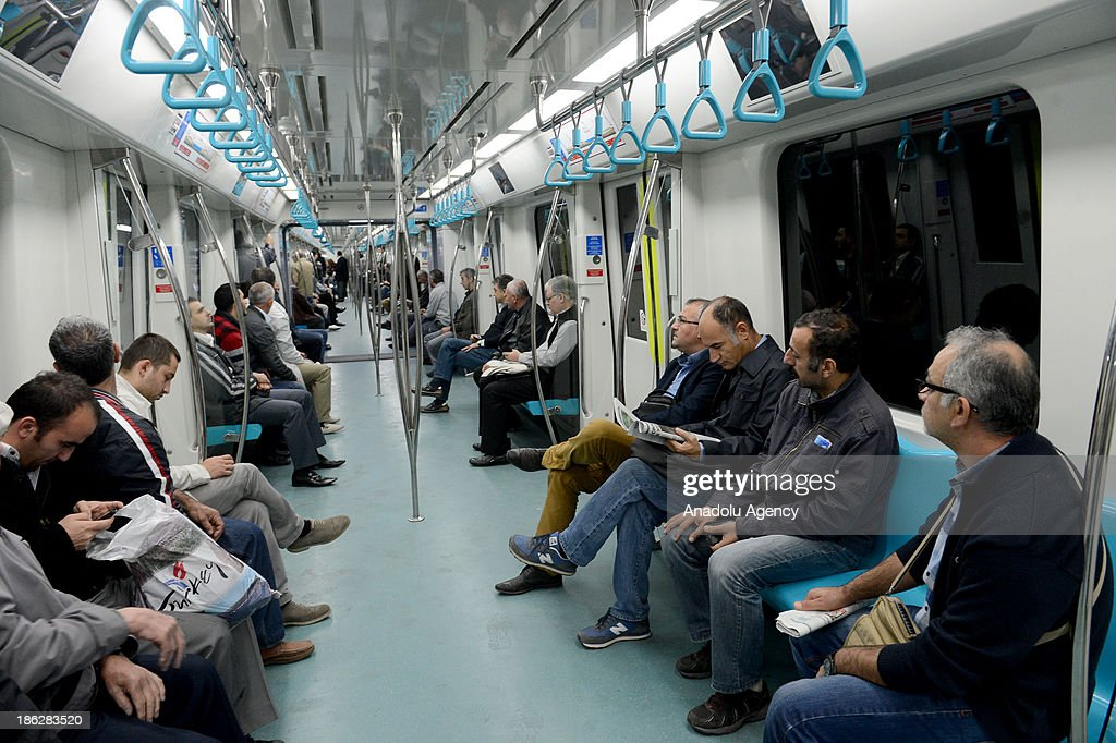 The passengers sit in the train during the The Marmaray journey on route Uskudar - Kazlicesme on the first day after its opening ceremony, October 30, 2013, Istanbul, Turkey. The Marmaray, the railway system linking the eastern and western sides of Istanbul from under the Marmara Sea, and Turkey's dream for 153 years, opened in Istanbul on the 90th anniversary of Republic of Turkey on October 29.