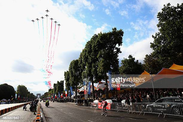 The Patrouille de France aerial display team flies overhead as the riders make their way down the Champs Elysees during the twenty first stage of the...
