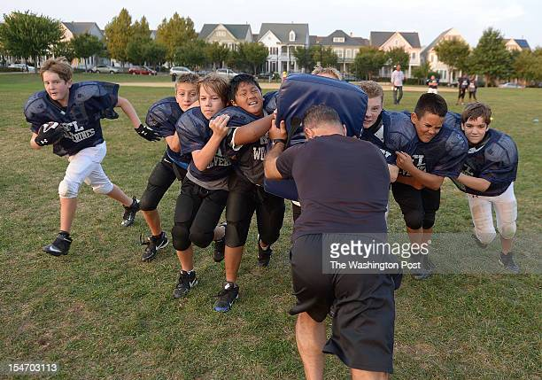 The Pee Wee Wolverines block for their running back as they push back Jon Berns during practice at Mattie Stepanek Park in Rockville on Wednesday...