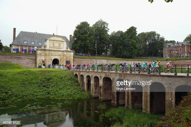 The peloton exit Arras Citadelle at the start of the sixth stage of the 2014 Tour de France a 194km stage between Arras and Reims on July 10 2014 in...