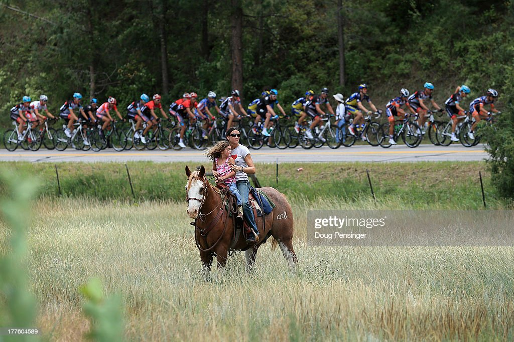The peloton passes horseback rider during stage six of the 2013 USA Pro Challenge from Loveland to Fort Collins on August 24, 2013 in Estes Park, Colorado.