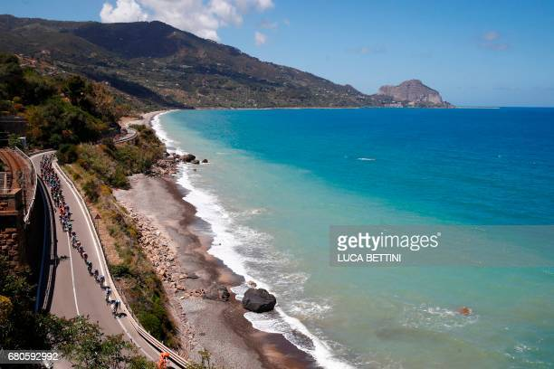 The peloton rides along the sea during the 4th stage of the 100th Giro d'Italia Tour of Italy cycling race from Cefalu to Etna volcano on May 9 2017...