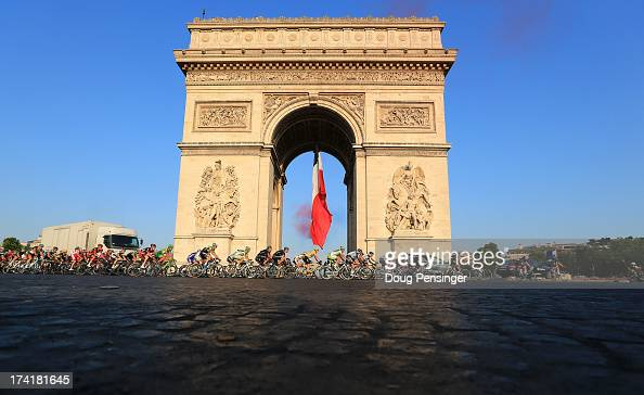 The peloton rounds the Arc d'Triomphe during the twenty first and final stage of the 2013 Tour de France a processional 1335KM road stage ending in...