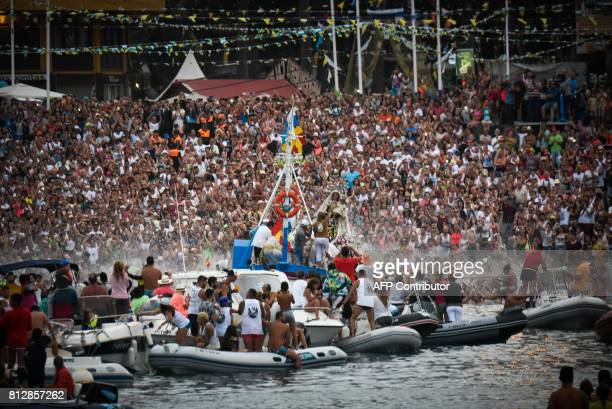 The penitents embark the Virgen del Carmen patron saint of fishermen to Puerto de la Cruz while the other costaleros have already embarked at San...