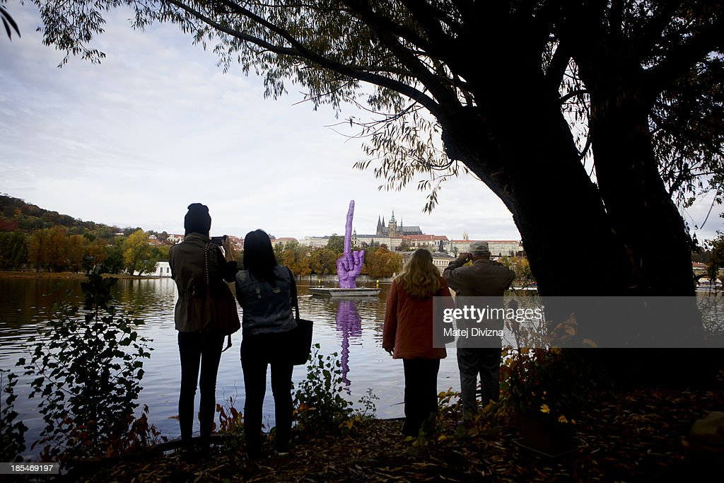 The people look on the sculpture with a rude gesture pointed to the Prague Castle, seat of the Czech President Milos Zeman, by Czech artist David Cerny is placed on Moldau river on October 21, 2013 in Prague, Czech Republic. David Cerny comments current political situation by his work earlier.