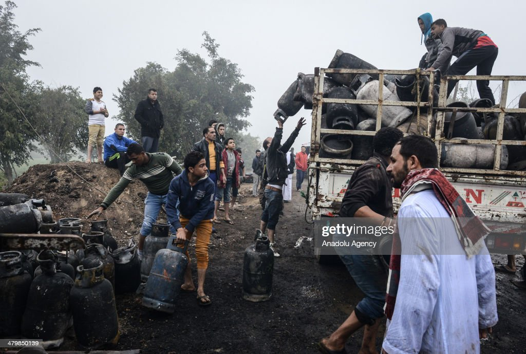 The people pick up the surrounding gas cylinders pieces. Egyptian fire fighters brought a fire at a gas cylinders storage under control in Giza, Egypt, on March 21, 2014. Gas cylinders went everywhere during the explosion.