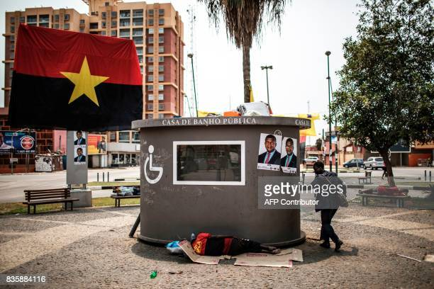 The People's Movement for the Liberation of Angola flags and electoral posters of the MPLA presidential Candidate Joao Lourenço are seen as a man...