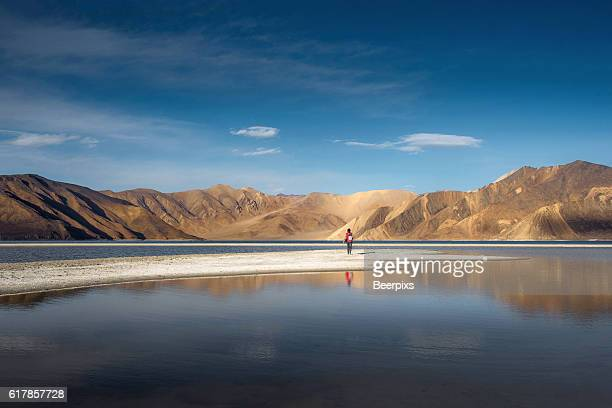 The person look at mountains in Pangong Lake and blue sky, Leh Ladakh.