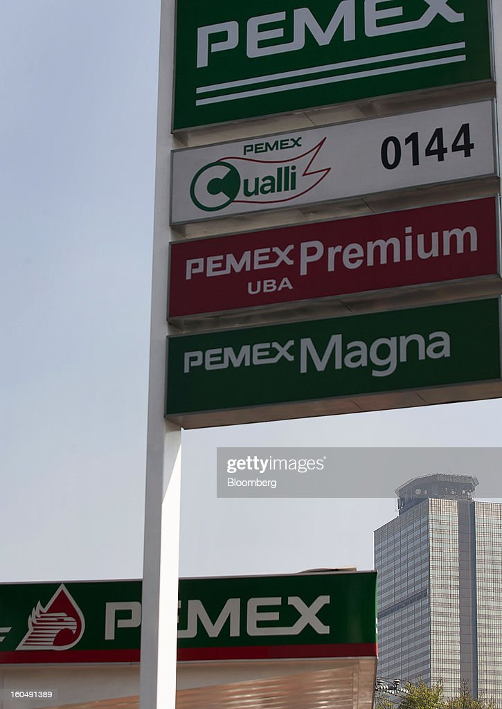The Petroleos Mexicanos (Pemex) administrative building stands in the distance past one of the company's gas stations in Mexico City, Mexico, on Friday, Feb. 1, 2013. Pemex is stepping up security at oil production facilities as authorities investigate a blast that killed at least 33 people at the state-owned company's headquarters in Mexico City yesterday. Photographer: Susana Gonzalez/Bloomberg via Getty Images