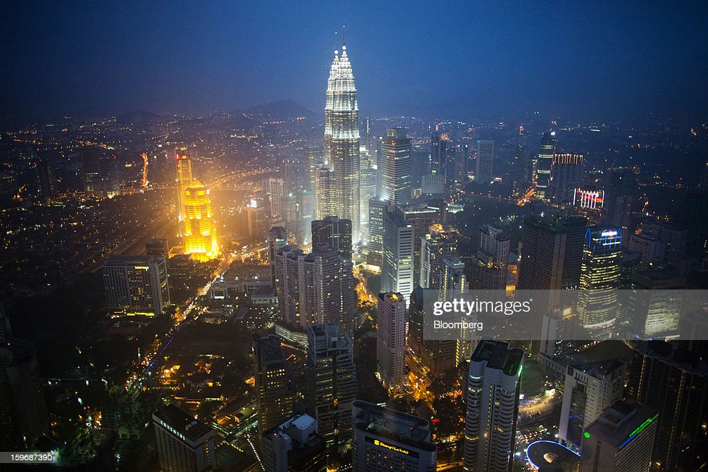 The Petronas Towers, center, stand illuminated at night in the central business district in Kuala Lumpur, Malaysia, on Wednesday, Jan. 16, 2013. While many developed countries have faltered, Malaysia's gross domestic product growth has exceeded 5 percent for five quarters with domestic demand countering a slowdown in exports. Photographer: Lam Yik Fei/Bloomberg via Getty Images