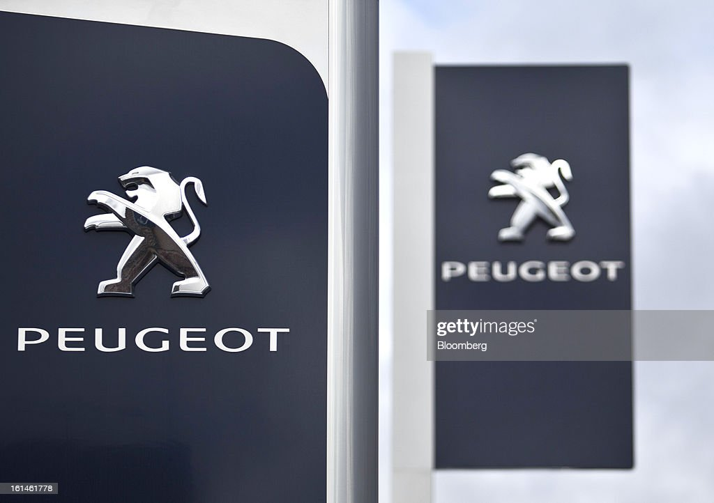 The Peugeot logo and flags are seen outside the Peugeot Sial Toulouse dealership in Toulouse, France, on Monday, Feb. 11, 2013. Europe's car market is forecast to drop to 12.3 million vehicles this year, 23 percent below the pre-crisis peak, IHS Automotive research company estimates. Photographer: Balint Porneczi/Bloomberg via Getty Images