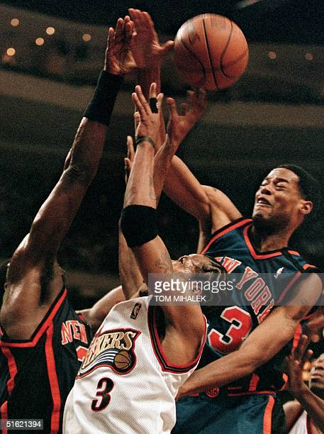The Philadelphia 76ers' Allen Iverson finds his way to the basket blocked by the New York Knicks' Patrick Ewing and Marcus Camby 19 February in...