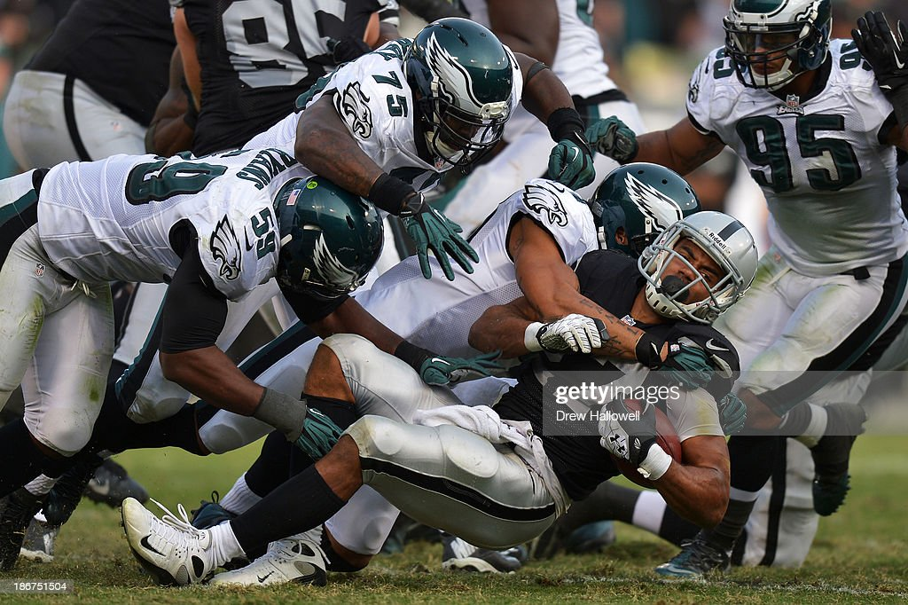 The Philadelphia Eagles gang tackle <a gi-track='captionPersonalityLinkClicked' href=/galleries/search?phrase=Rashad+Jennings&family=editorial&specificpeople=2250821 ng-click='$event.stopPropagation()'>Rashad Jennings</a> #27 of the Oakland Raiders at O.co Coliseum on November 3, 2013 in Oakland, California. The Eagles won 49-20.