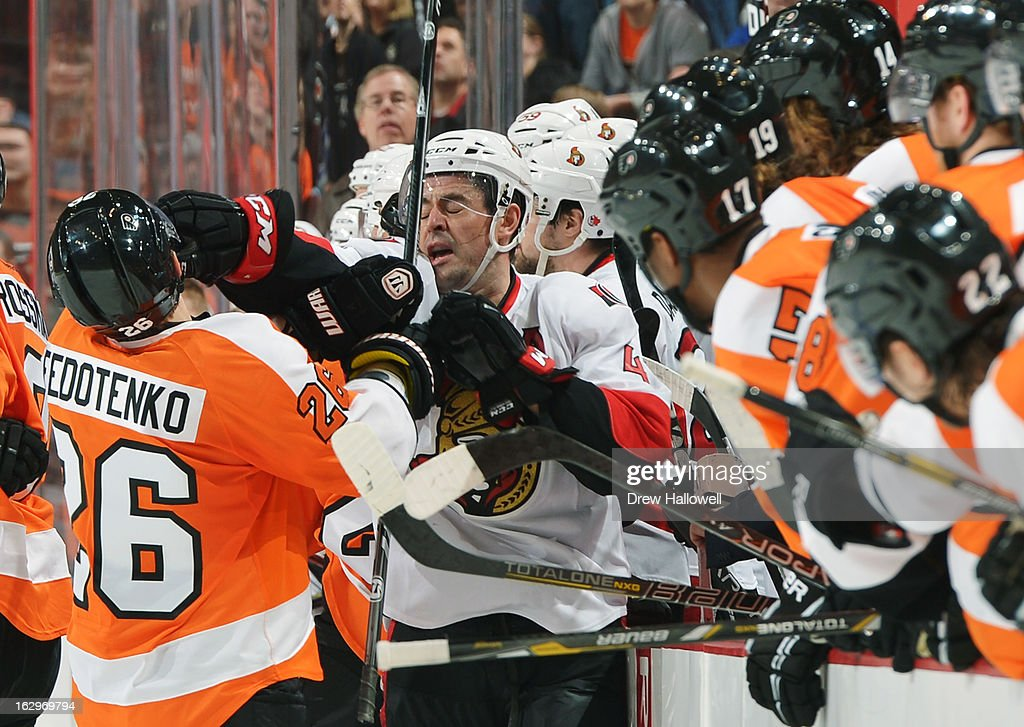The Philadelphia Flyers watch as teammate Ruslan Fedotenko #26 takes a glove to the face from Chris Phillips #4 of the Ottawa Senators at the Wells Fargo Center on March 2, 2013 in Philadelphia, Pennsylvania.
