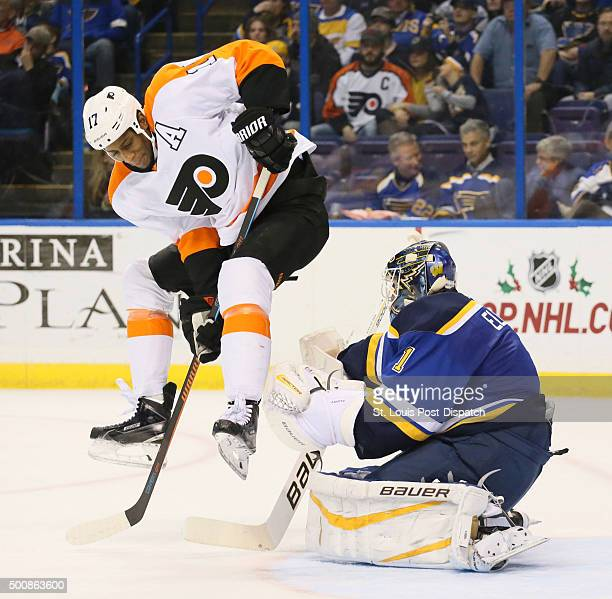 The Philadelphia Flyers' Wayne Simmonds left tries to hop clear of a teammate's shot as St Louis Blues goaltender Brian Elliott defends in the second...