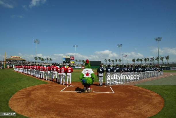 The Philadelphia Phillies and New York Yankees line up with the Philly Fanatic during the National Anthem prior to their game on March 4 2004 at...