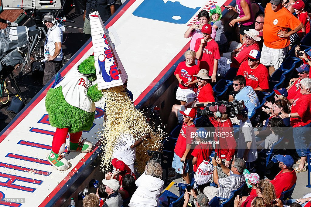 The Philadelphia Phillies mascot the Phillie Phanatic dumps popcorn on a Washington Nationals fan in the stands during the game at Citizens Bank Park on August 26, 2012 in Philadelphia, Pennsylvania. The Phillies won 4-1.