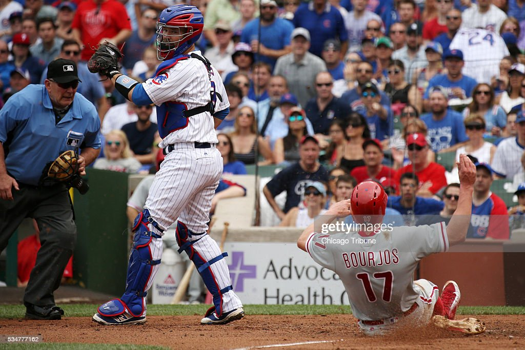 The Philadelphia Phillies' Peter Bourjos (17) scores ahead of the tag by Chicago Cubs catcher David Ross (3) on a sacrifice fly by Philadelphia's Maikel Franco during the third inning on Friday, May 27, 2016, at Wrigley Field in Chicago.