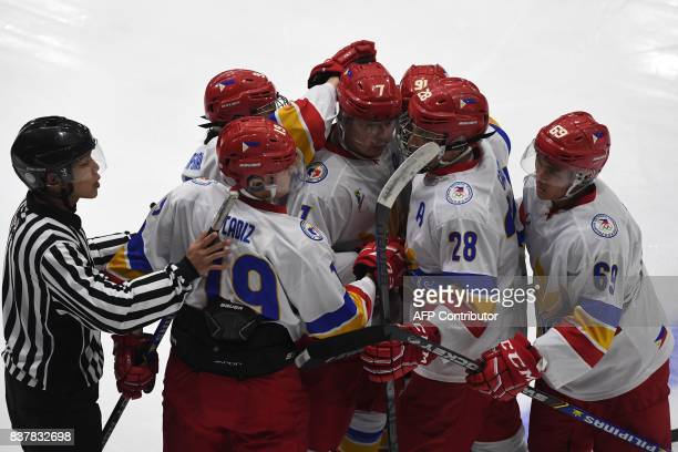 The Philippines ice hockey team celebrates a goal during their round robin ice hockey game against Malaysia during the 29th Southeast Asian Games in...