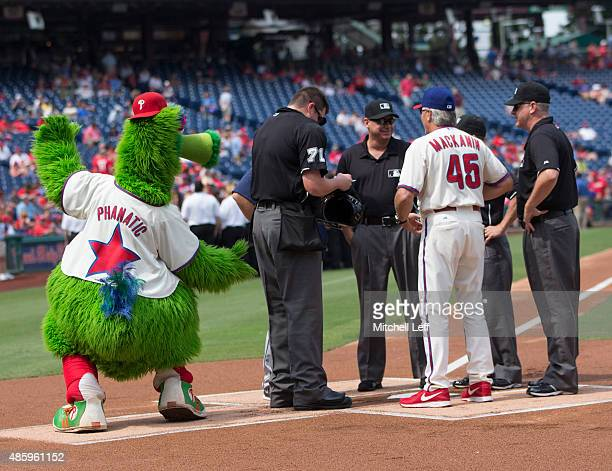 The Phillie Phanatic attempts to pinch the behind of umpire Jordan Baker prior to the game between the San Diego Padres and Philadelphia Phillies on...