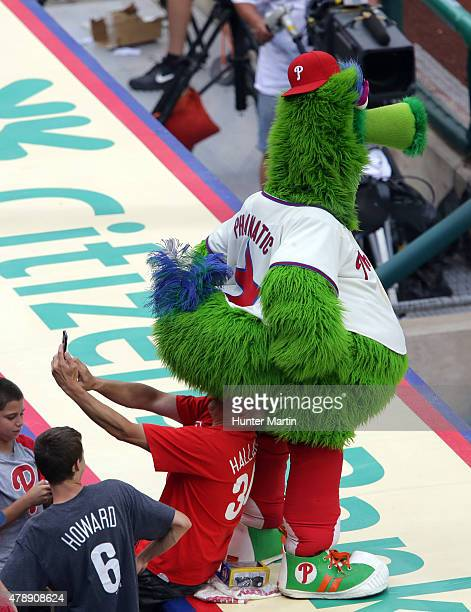The Phillie Phanatic sits on the head of a fan as he takes a photo during game two of a doubleheader against the Philadelphia Phillies at Citizens...