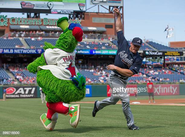 The Phillie Phanatic wrestles with Anthony Recker of the Atlanta Braves prior to the game at Citizens Bank Park on September 4 2016 in Philadelphia...