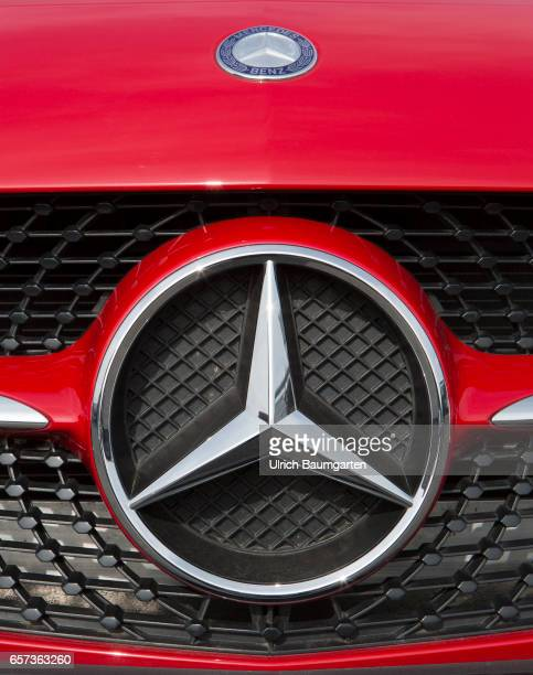 The photo shows the Mercedes Benz logo on a Mercedes car