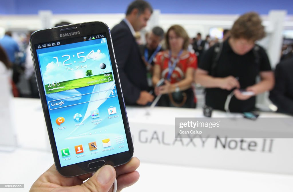 The photographer holds up a Samsung Galaxy Not II mini tablet during a press day at the Samsung stand at the IFA 2012 consumer electronics trade fair on August 30, 2012 in Berlin, Germany. IFA 2012 will be open to the public from August 31 through September 5.