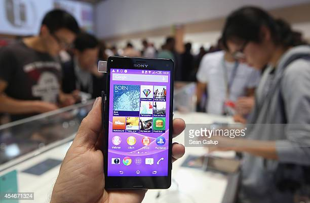 The photographer holds up a Sony Xperia Z3 smartphone at the Sony stand at the 2014 IFA home electronics and appliances trade fair on September 5...