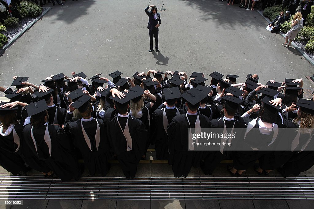 The photographer instructs students to adjust their mortartboards at the University of Birmingham as they graduate on July 14, 2009 in Birmingham, England. Over 5000 graduates will be donning their robes this week to collect their degrees from The University of Birmingham. A recent survey suggested that there are 48 graduates competing for every job.