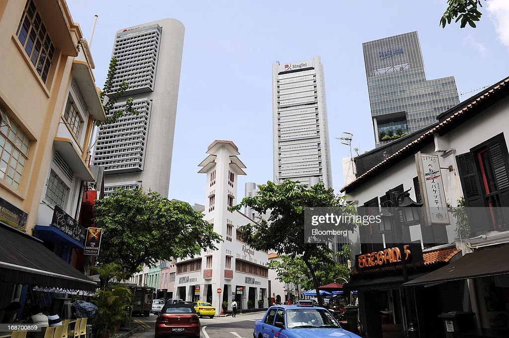 The Pickering Operations Complex buiding, center right, operated by Singapore Telecommunications Ltd. (SingTel), stands between the OCBC Center building, left, and the One George Street building in Singapore, on Tuesday, May 14, 2013. SingTel, southeast Asia's largest phone company, is scheduled to release fourth-quarter earnings on May 15. Photographer: Munshi Ahmed/Bloomberg via Getty Images