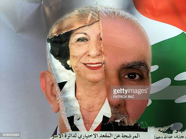 The picture of a female candidate for Beirut's municipal elections appears under a teared picture of a male candidate on a wall in the Lebanese...