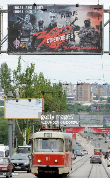 The picture taken in eastern Ukrainian city of Donetsk on June 25 2014 shows an advertising billboard reading 'Steel Russians' and depicting...