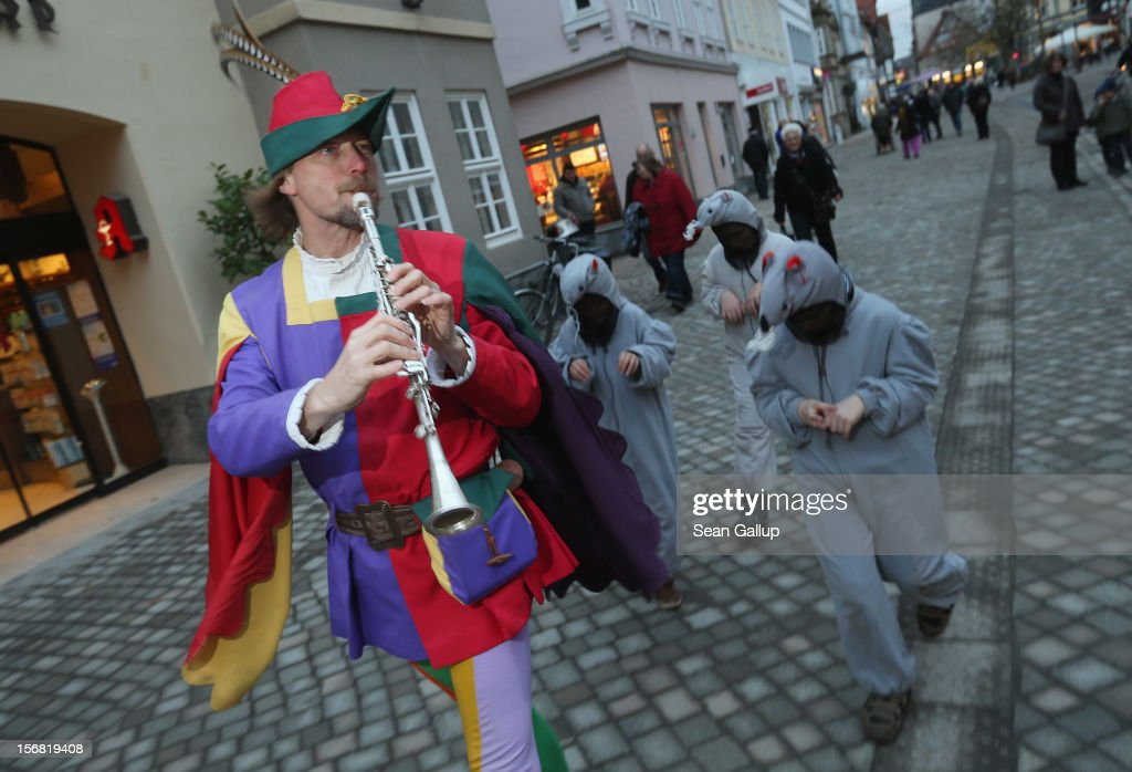 The Pied Piper of Hamelin, actually city tourism employee Michael Boyer, leads local children dressed as rats through a pedestrian shopping street on November 19, 2012 in Hameln, Germany. The Pied Piper (in German: Der Rattenfaenger), is one of the many stories featured in the collection of fairy tales collected by the Grimm brothers, and the 200th anniversary of the first publication of the stories will take place this coming December 20th. Boyer, a U.S. citizen who has lived in Hameln for 15 years, and city children regularly perform a reenactment of the Pied Piper tale throughout the summer months. The Grimm brothers collected their stories from oral traditions in the region between Frankfurt and Bremen in the early 19th century, and the works include such global classics as Sleeping Beauty, Little Red Riding Hood, Rapunzel, Cinderella and Hansel and Gretel.