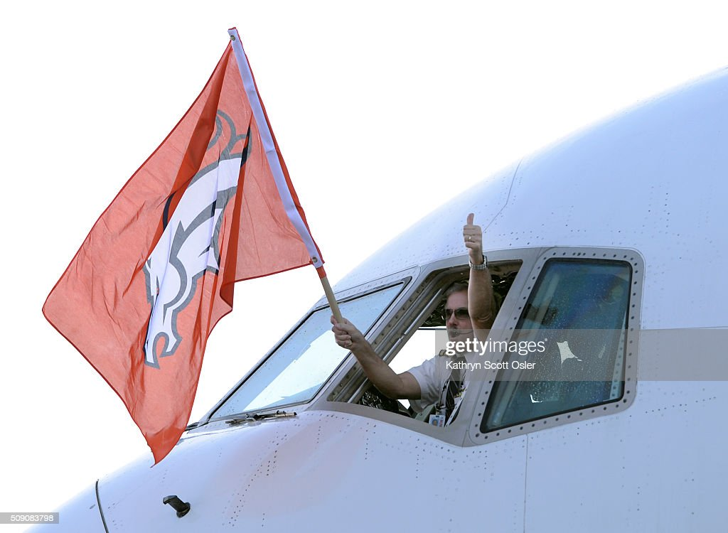 The pilot gives a thumbs-up and waves a team flag as members of the Denver Broncos football team arrive home at Denver international Airport on Monday, Feb. 8, 2016.