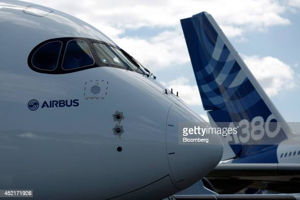 The pilot's windows of an Airbus A350 widebody aircraft produced by Airbus Group NV left sit above the nose cone as it stands on display near the...
