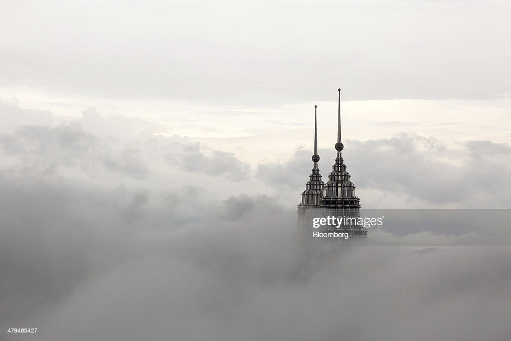 The pinnacles of the Petronas Twin Towers protrude through low clouds in Kuala Lumpur, Malaysia, on Tuesday, March 18, 2014. Malaysia, aspiring to become a developed nation in six years, is finding that more than 50 years under one coalition and tight control over information is a mismatch for handling a rapidly growing crisis followed across the world. Photographer: Charles Pertwee/Bloomberg via Getty Images