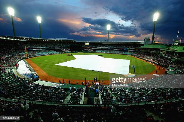 The pitch is covered as a storm approaches before the start of play during the opening match of the MLB season between the Los Angeles Dodgers and...