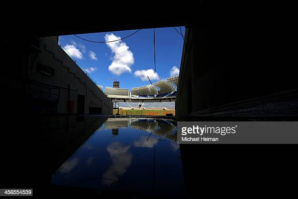 The pitch is seen reflected in a puddle of water as construction continues at the Estadio das Dunas on December 13 2013 in Natal Brazil The stadium...